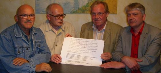 Paul Mattick, Josef Heinrich, Werner Schmidt und Lothar Schmidt halten die Kopie der Schuldverschreibung von 1212 in Händen